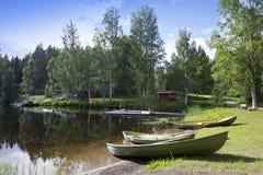 Barcos en el banco del lago del bosque Imagenes de archivo