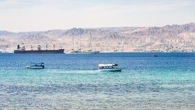 Barcos en el golfo de Aqaba y la vista de la ciudad de Eilat Imagen de archivo