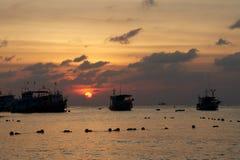 Barcos en el mar en la puesta del sol Imagen de archivo