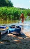 Barcos en el muelle, muchacha alegre con los remos en sus manos Imagen de archivo libre de regalías