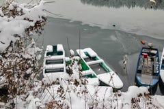 Barcos en el río congelado cubierto con nieve imagen de archivo