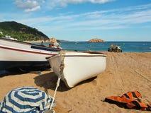 Barcos en la arena en la bahía de Costa Brava Imagenes de archivo