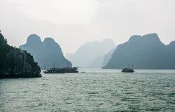 Barcos en la niebla en la bahía de Halong Imagen de archivo