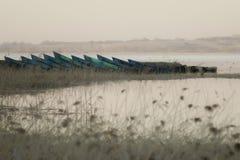 Barcos en la orilla del lago, en el fondo de la puesta del sol Fotografía de archivo libre de regalías