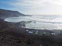 Barcos en la orilla volcánica negra cerca del EL Golfo, Lanzarote Imágenes de archivo libres de regalías