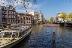 Barcos en puerto en el canal cerca del puente en Amsterdam Fotos de archivo