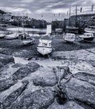 Barcos en puerto en el Mousehole, Cornualles durante la bajamar Fotografía de archivo libre de regalías
