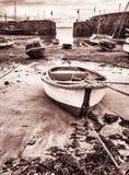 Barcos en puerto en el Mousehole, Cornualles durante la bajamar Fotos de archivo