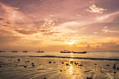 Barcos en puesta del sol caliente en costa del océano Foto de archivo libre de regalías