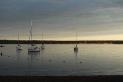 Barcos en un lago en la salida del sol Foto de archivo libre de regalías