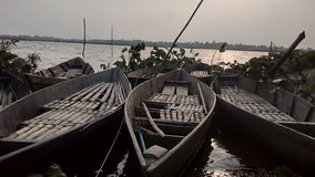 3 barcos fluyen en el banco del río en el tiempo de la puesta del sol Fotografía de archivo