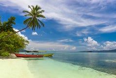 Barcos locais de duas cores na costa da ilha, na praia tropical com palma de coco, na areia branca e na água de turquesa fotos de stock royalty free