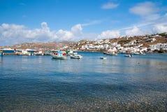 Barcos na água do mar em Mykonos, Grécia Vila do mar no céu azul nebuloso Casas brancas na paisagem da montanha com agradável Foto de Stock