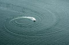 Barcos na água que faz círculos imagens de stock