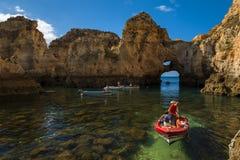 Barcos na baía pequena entre os penhascos do arenito no Ponta a Dinamarca Piedade em Lagos, Portugal fotografia de stock royalty free