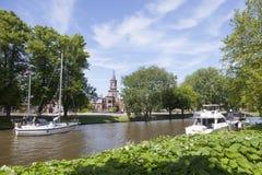 Barcos no canal perto do centro da cidade holandesa velha leeuwarden com chu Foto de Stock
