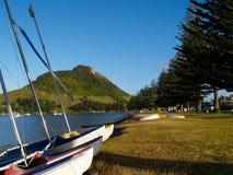 Barcos no primeiro plano da montagem Maunganui. fotografia de stock royalty free