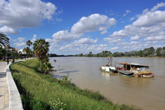Barcos pequenos no rio como passa através de Coria del Rio, província de Sevilha, a Andaluzia de Guadalquivir, Espanha Imagem de Stock