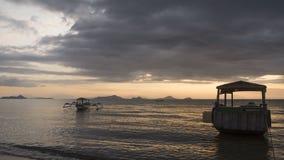 Barcos que flotan en la puesta del sol Fotografía de archivo libre de regalías