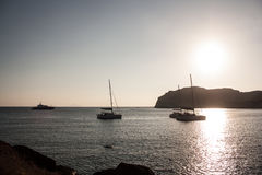 Barcos que flotan en la puesta del sol Fotos de archivo libres de regalías