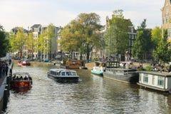 Barcos turísticos en el canal de Amsterdam, los Países Bajos imagenes de archivo