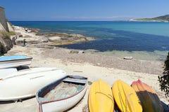 Barcos y canoas en la playa alejada por el mediterráneo Imagen de archivo libre de regalías