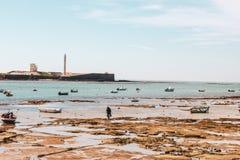 Barcos y marea en la playa de Cádiz en Andalucía, España imagen de archivo