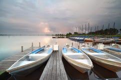 Barcos y yates por el embarcadero durante puesta del sol lluviosa Fotografía de archivo
