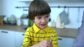 Bardzo śliczna chłopiec trzepie jajko w kuchni gramolący się kulinarni jajka Atrakcyjny ojciec i bardzo śliczna chłopiec robimy zbiory wideo
