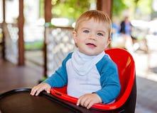 Bardzo śliczny piękny chłopiec obsiadanie w highchair czerni Obraz Royalty Free