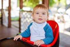 Bardzo śliczny piękny chłopiec obsiadanie w highchair czerni Fotografia Royalty Free