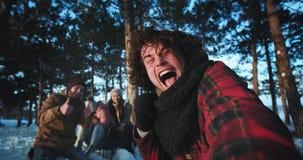 Bardzo atrakcyjni przyjaciele w zima czasie i jeden młody facet trzyma kamerę z kędzierzawym włosy i robią selfie wideo zbiory