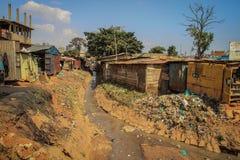 Bardzo brudna rzeka z banialukami i górami klingeryt na bankach wśród biednych domów w slamsach zdjęcie stock