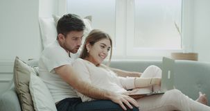 Bardzo charyzmatyczna para uśmiechnięta i szczęśliwa robi rozkazowi oba w piżamach od notatnika w ranku na kanapie zdjęcie wideo