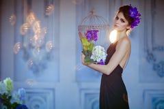 Bardzo piękna brunetki kobieta z kwiatami w jej włosianym trzyma c obraz stock