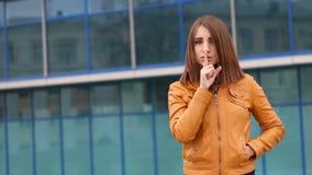 Bardzo piękna dziewczyna robi cisza gestowi plenerowy w mieście przy kamerą zbiory wideo