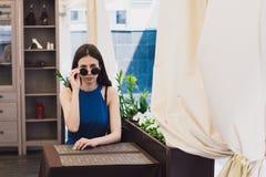 Bardzo piękna dziewczyna siedzi w kawiarni w czarnych round szkłach fotografia royalty free