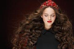 Bardzo piękna wspaniała dziewczyna z czerwoną tiarą i eleganckim spływaniem Zdjęcia Stock
