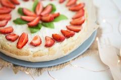 Bardzo piękny lata cheesecake dekorował z truskawkami - stojaki na białym drewnianym stole, w górę obrazy royalty free