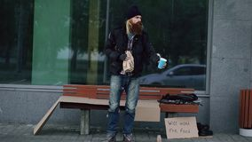 Bardzo pijący bezdomny mężczyzna z kartonu i alkoholu znakiem błaga dla pieniądze przy chodniczkiem podczas gdy trwanie pobliska  zdjęcie royalty free