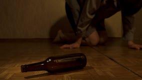 Bardzo pijący mężczyzna kłama na podłoga w pokoju Butelka jest na podłoga zdjęcie wideo