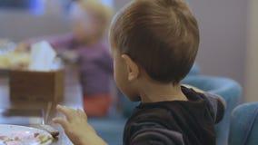 Bardzo przystojna chłopiec wkurza kogoś i ono uśmiecha się przy kamerą w kawiarni 4K zbiory wideo