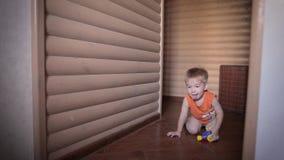 Bardzo szczęśliwa dwa roczniaka dziecka chłopiec kłama na podłodze i bawić się z zabawkarskim samochodem zdjęcie wideo