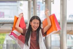 Bardzo szczęśliwa młoda kobieta z torba na zakupy, przy centre lub centrum handlowym sa Zdjęcie Royalty Free