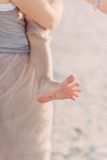 Bare baby foot in the sand. On the beach at mum on hands of the baby and children's foot barefoot in the sand Royalty Free Stock Images