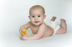 Bare Baby on Tummy with Rubber Ducky. Baby in diaper on tummy playing with a rubber ducky royalty free stock images