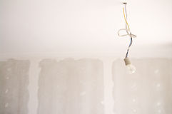 Bare bulb in new home. Bare bulb hanging on wire in a new home Stock Image