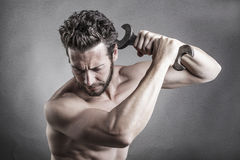 Bare chest man using a spanner or wrench as a weapon Stock Photos