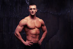 Bare-chested handsome man with reliefed muscles standing half-tu Royalty Free Stock Photography