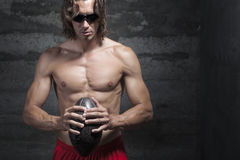 Bare chested long hair muscle man is wearing sungl. Asses and holding football ball in hands Royalty Free Stock Images